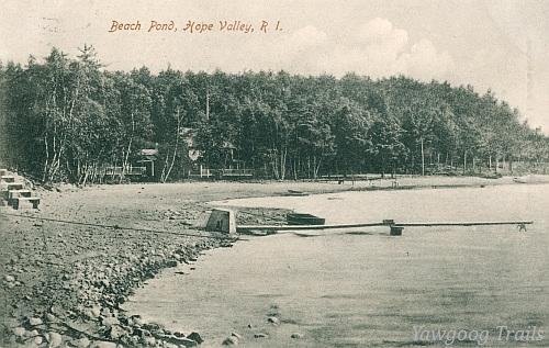 Black and white postcard of a cottage on the forested shore of the pond.