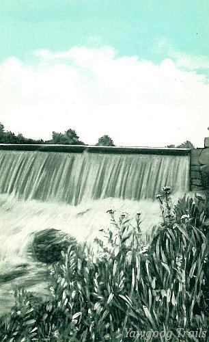 Black and white postcard of a water flowing over a dam with a tinted blue sky and white clouds