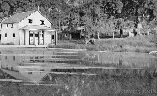 Black and white postcard of a white building on the shore of the pond.