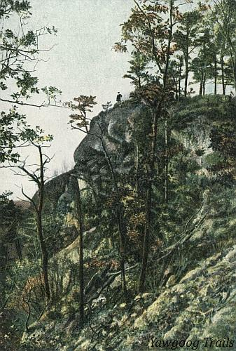 Color lithographed postcard of man standing atop cliff.