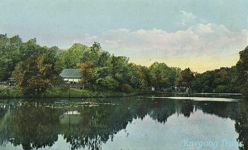 Color lithographed postcard of a house beside a pond.