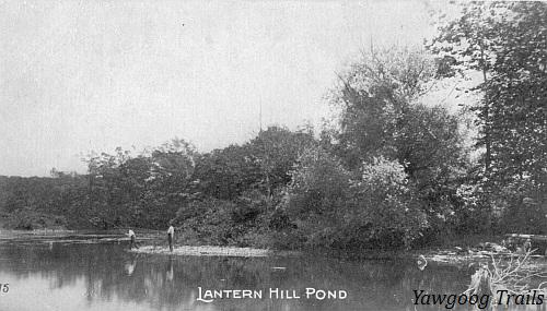 Black and white postcard of two men fishing a pond's edge.