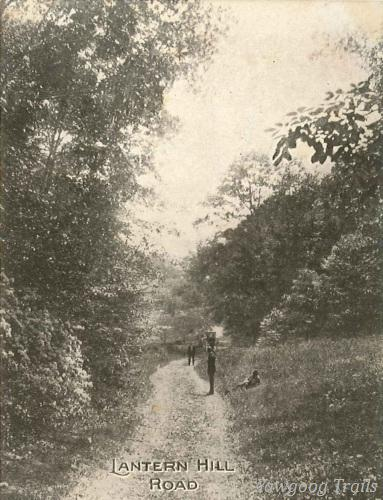 Black and white postcard of two men standing on a dirt road.  A third man is sitting in the grass beside the road.