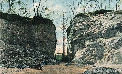 Color lithographed postcard of quarry, showing a gateway between two white cliffs